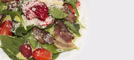 Delicious and healthy salad with arugula, strawberry, cheese and bacon. background