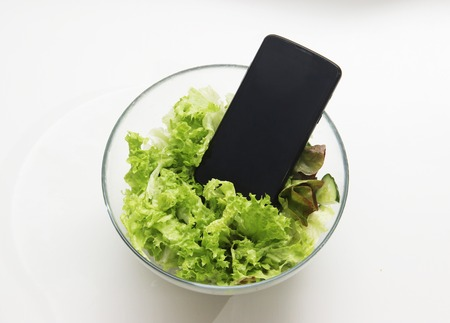 Smartphone in the salad. Symbol of dependence on social networks, putting pictures of food in social networks. You can use it as an illustration of calorie counting using gadgets, diet, proper nutrition.
