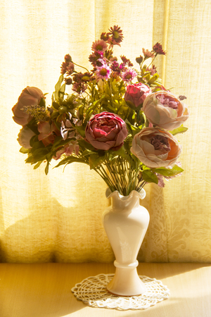Beautiful artificial flowers of peonies and chrysanthemums in a delicate pink vase on a warm ocher yellow background.