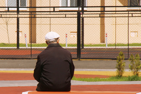 A lonely old man sits on a bench with his back to us and looks at the sports basketball court. A symbol of old age, loneliness, ill health and the desire to become young again Stock Photo