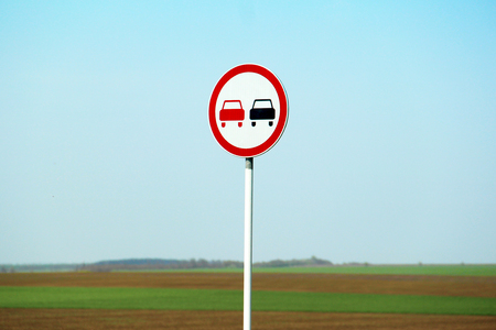 Road sign overtaking is prohibited on the highway against the backdrop of the blue sky. Stock Photo