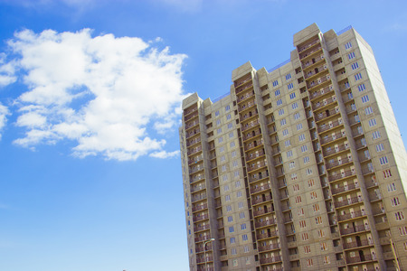 New uncompleted residential high-rise building of reinforced concrete slabs on the background of the blue sky. Social programs and affordable housing for young families. Construction industry. Archivio Fotografico
