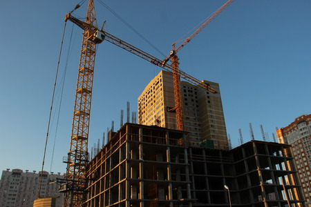 Building of a Of a multi-storey residential building with two tower cranes. Construction of a monolithic frame building. Stock Photo