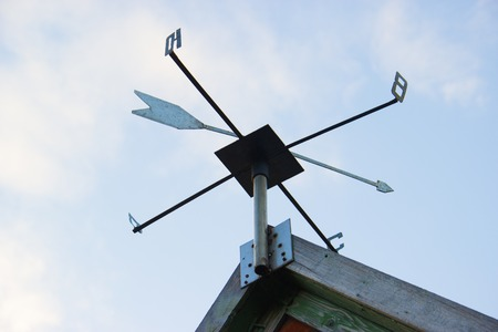 Weathervane Against a Radiant Blue Sky. The sides of the world are marked with Cyrillic letters. Weather vane of Russia and CIS countries. Stock Photo