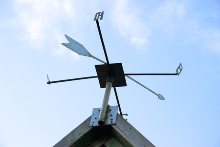 Weathervane Against a Radiant Blue Sky. The sides of the world are marked with Cyrillic letters. Weather vane of Russia and CIS countries, Stock Photo
