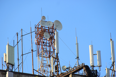 Telecommunication base stations network repeaters on the roof of the building. The cellular communication aerial on a building roof. Cell phone telecommunication tower. Antennas on top of building Stock Photo