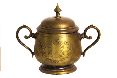 An old brass or bronze metal sugar bowl with a lid and ornament. Metal punctles with scratches and patina Stock Photo