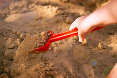 Red plastic scoop scoop in a childrens hand. Play in the sandbox. With a scoop of sand falls. Symbol of childhood and fun.