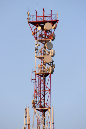 Telecommunications tower and satellite dish telecom network on blue sky with bright sun light. Stock Photo
