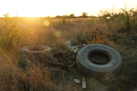 spontaneous dump discarded tires and household rubbish . garbage dump on the side of a dirt road. The problem of recycling garbage, tires. Garbage removal Zdjęcie Seryjne