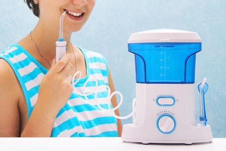 bella ragazza lava i denti con un irrigatore orale. la donna sorride e tiene in mano l'irrigatore. pulizia dei denti a casa con un dispositivo compatto. Pulizia dei denti con getto d'acqua sotto pressione.