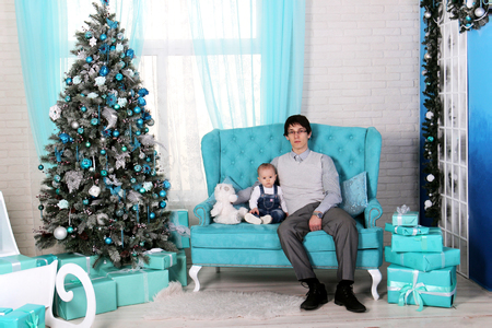 Cristmas: father and child sitting on sofa in Christmas interior near Christmas tree.. One year old girl with dad and a bear meets the first happy new year 2018. Blue delicate light interior Happy family