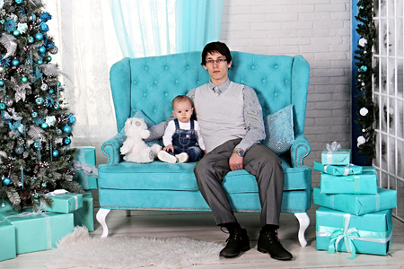 father and child sitting on sofa in Christmas interior near Christmas tree.. One year old girl with dad and a bear meets the first happy new year 2018. Blue delicate light interior Happy family