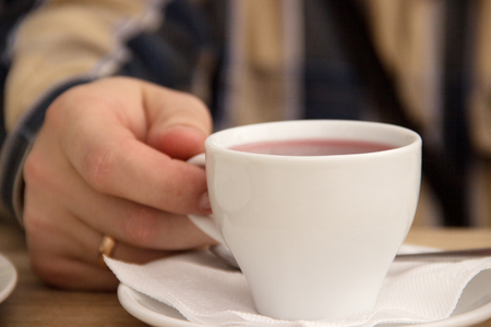 man's: A caucasian mans hand holds a white cup with red herbal tea. Wooden table. Peace and tranquility during the break. Ring on hand.