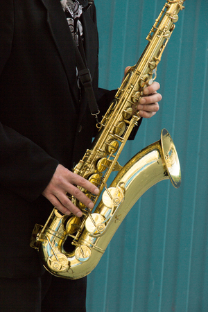 close up of street saxophone Player hands playing alto sax musical instrument over blue background , closeup with copy space, can be used for music background