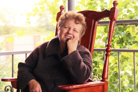 a portrait of an old thoughtful woman. Grandmother sits in an armchair on the terrace and smile. Archivio Fotografico