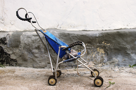 derelict and dis guarded old and dirty vintage pram of pushchair dumped in an old background. Summer stroller as a symbol of a bygone childhood. Stock Photo