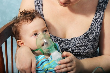 Little cute girl doing inhalation at home. Two year old baby inhaling from the inhaler, mother holding her in arms. sick child. Treatment of cough or asthma. child in mask for inhalations. Blue color