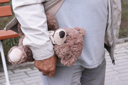 a teddy bear in the hand of a man. old person walk on the street. Grandpa holds a toy of a grandson or granddaughters child.