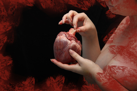 real human heart in beautiful female hands. symbol of love, pain. Insidious nude girl with heart of man. Feminism or patriarchy. postcard st Valentine's Day. Love causing pain. Low key.