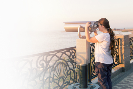 Young girl in white t-shirt looking through a coin operated binoculars on the sea shore. Woman look in touristic telescope on embankment. Stock Photo