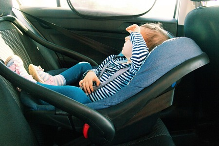 baby smile in a safety car seat. security. one year old child girl in blue wear sit on auto cradle. Rules for the Safe Transport of Children. Holders.