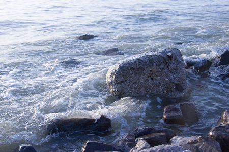 View of dawn at the seaside with the clear sky. surf waves and large boulder stones. Blue background with copy space. 写真素材