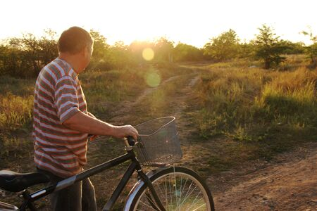 Old man riding bike on country dirt road towards the sunny sunset sky. Grandfather is rolling a bicycle. Walk outdoors. Healthy lifestyle. Meadow grass trees warm summer evening. Copy space for text 스톡 콘텐츠