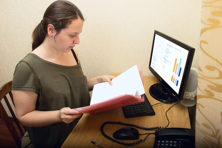 A young girl with excess weight and long hair examines documents. Work in the office. On the computer graphics monitor. Nearby phone and office supplies. Accounting, management. No dress code.