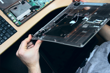 man with a screwdriver is repairing computer equipment. his hands and details of the device. repair shop for gadgets. Disassembly of an old laptop. Master removed the screen and holds it in his hands.