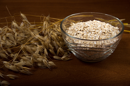 Oat ears stems and oat flakes in a bowl on a dark brown wood background. oat flakes small size grind. Copy space in bottom. Useful fiber-rich product. Dietary breakfast from healthy foods. Stock Photo