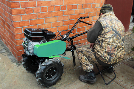 a man sits and prepares a green motor-cultivator with a gasoline engine to work. Repair and service. red brick wall in the background. Copy space for text.