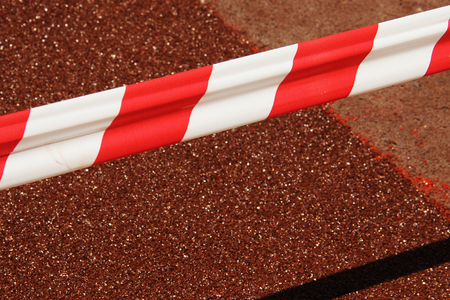red white barricade on red background.Realistic red and white danger tapefences the place of repair of the old covering. Fresh patch of rubber crumb on the stadium cover freezes and gains strength