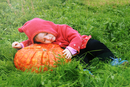 a little girl lie down on a huge pumpkin in a magical meadow. The baby is wearing a gnome costume. Magic and fireflies. Can be used as a card for halloween holiday