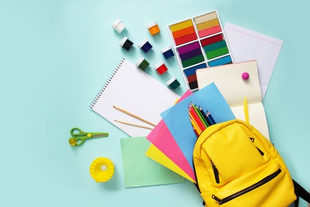 School stationary supplies sets and knapsack on blue background. Top view. Reklamní fotografie