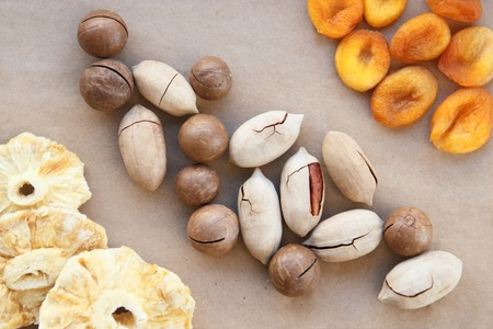 macadamia, Brazil nuts, Bertholletia, pecan dried pineapples and apricots on brown wrapping paper. roasted and notched exotic shell nuts background