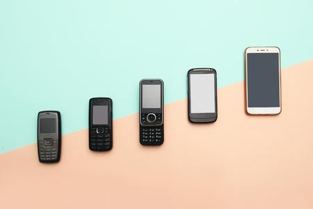 évolution des téléphones portables. Concept de téléphone et de pda de développement technologique. Téléphones anciens et nouveaux. Vue de dessus. Progrès de la communication téléphonique, appareil mobile classique