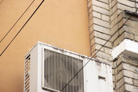 parte de la fachada del edificio con púas de plástico contra palomas. el diseño no permite que los pájaros se sienten y caguen. Los picos de plástico verticales en dos filas mantienen los acondicionadores de aire lejos de los excrementos. Foto de archivo