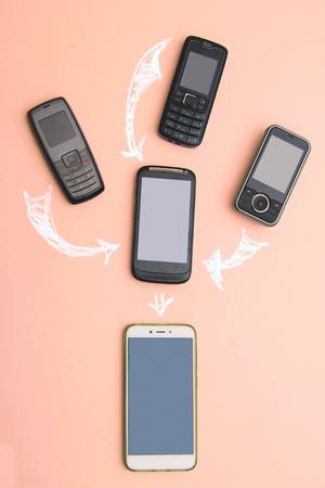 携帯電話の進化。技術開発電話とpdaの概念。ヴィンテージと新しい携帯電話。トップ ビュー。電話通信の進捗状況、モバイルクラシックデバイス.グラフ、矢印、テキスト