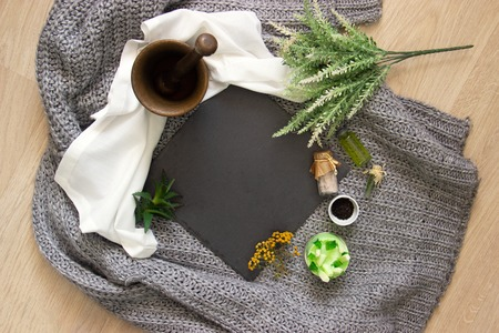 natural slate slab surrounded by herbs, alchemy appliances, potions and ingredients lies on a table. fabric linen and knitted around. Halloween occultism background. Flat lay with copy space for text. spirit halloween.