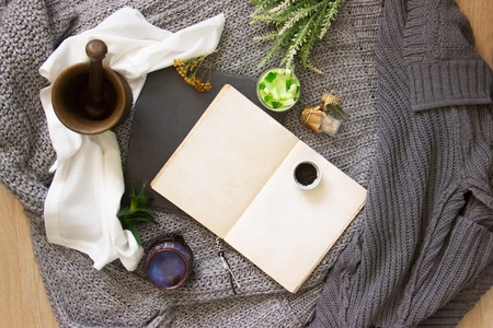vintage notebook surrounded by herbs, alchemy appliances, potions and ingredients lies on natural slate slab wooden table. Halloween occultism background. Flat lay with copy space for text. Imagens