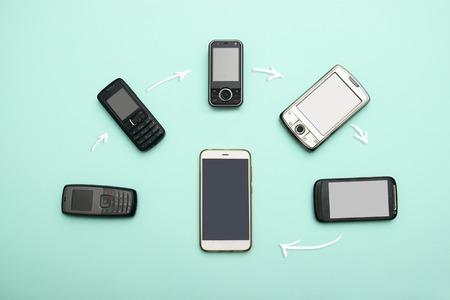 Entwicklung der Handys. Technologieentwicklungstelefon und PDA-Konzept. Vintage und neue Telefone. Ansicht von oben. Fortschritt der Telefonkommunikation, mobiles klassisches Gerät . Diagramme, Pfeile, Text herum Standard-Bild