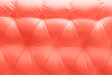 genuine leather upholstery chesterfield style texture painted Living coral color background. Color of the year 2019. Main trend concept.