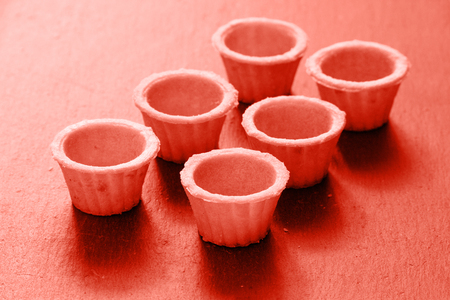 Empty tartlets Living coral color background. Color of the year 2019. Main trend concept