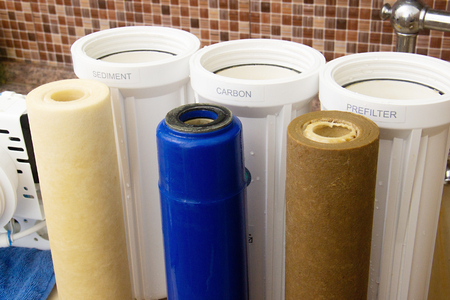 three dirty used osmosis water filter cartridges
