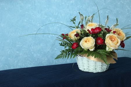 Beautiful yellow rose in white basket on a blue background with copy space for text Imagens