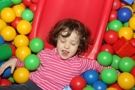 Little curly cute smile girl plays in balls for a dry pool. Play room. Happiness.