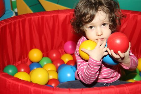 Little curly cute smile girl plays in balls for a dry pool. Play room. Happiness. the child has hands full of balls