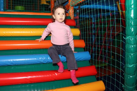 little cute curly baby girl playing in a childrens entertainment center in the game maze. The child plays in the playground Zdjęcie Seryjne