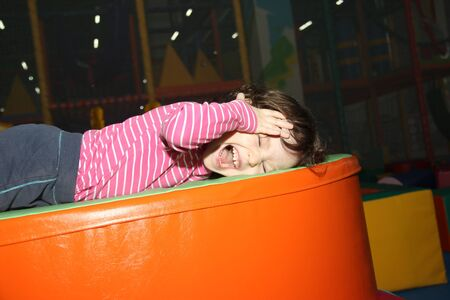 little cute curly baby girl lie oranges trampoline against a dark black ceiling with longitudinal ceiling lights. baby playing in a children's entertainment center in the game maze the playground. she close head and scream.